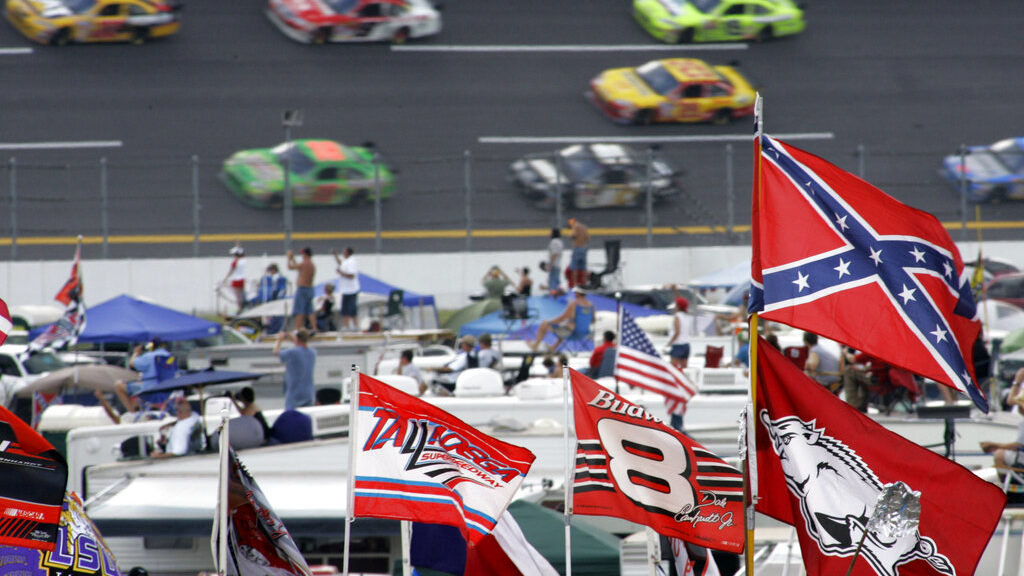 A Confederate flag flies in the infield as cars come out of Turn 1 during a NASCAR auto race at Talladega Superspeedway in Alabama